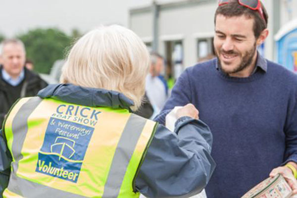 Volunteer greets visitor to Crick Boat Show